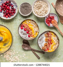 Healthy clean breakfast with smoothie bowl with mango and  tropical fruits , chia seeds yogurt pudding and cranberries, nuts, oatmeal topping in coconut shells with spoon, top view.