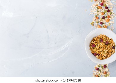 Healthy clean eating, dieting and nutrition, fitness, balanced food, breakfast concept. Homemade granola muesli with ingredients on a table. Top view flat lay copy space background