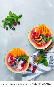 Healthy clean eating, dieting and nutrition, seasonal, summer breakfast concept. Fruit salad with yogurt in carved watermelon bowl on a kitchen table. Top view flat lay background.
