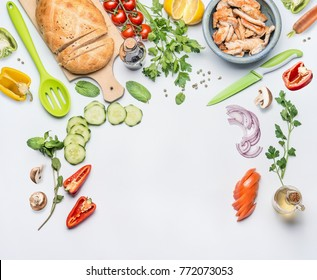 Healthy clean eating layout for lunch food and diet nutrition concept. Various fresh vegetables ingredients for salad with green cooking spoon and knife on white table background, top view, frame