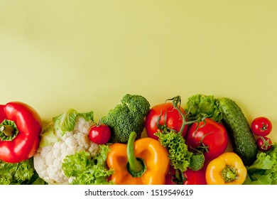 Healthy clean eating layout, vegetarian food and diet nutrition concept. Various fresh vegetables ingredients for salad on yellow table background, top view, frame, banner
