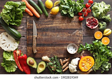Healthy clean eating, plant based layout, vegetarian food and diet nutrition concept. Various fresh vegetables ingredients for cooking on dark wooden table