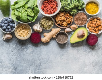 Healthy clean food  - vegetables, fruits, nuts, superfoods on a gray background.  Healthy eating concept. Top view. Copy space