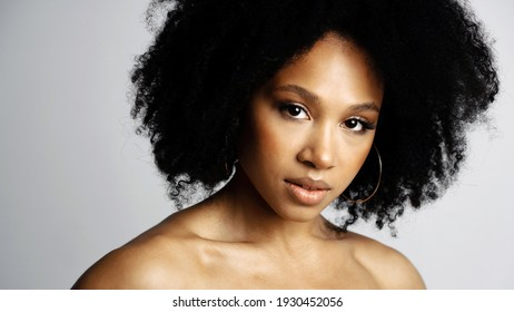 Healthy, Clean, perfect facial skin. Beauty Portrait of a young female model of Afro-appearance posing. Working in a photo studio on a white background. Black healthy curly hair