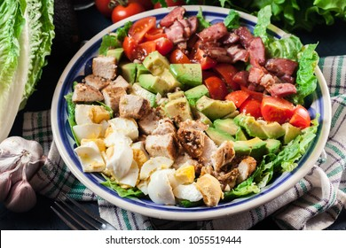Healthy cobb salad with chicken, avocado, bacon, tomato, and eggs. American dish