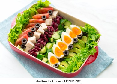 Healthy cobb salad with chicken, avocado, cucumber, tomato, olive, and eggs. American dish