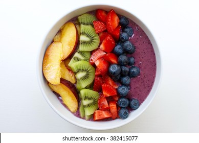 Healthy and colorful breakfast acai smoothie bowl with fruit toppings