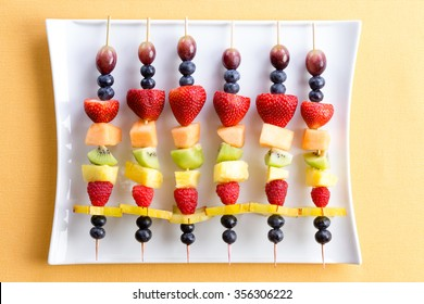 Healthy colorful fresh shish kebab fruit treats made from seasonal summer tropical fruit arranged neatly in a row on a modern white rectangular platter on a yellow textured table viewed from above