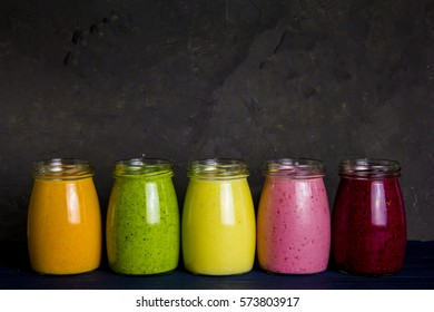 Healthy colorful fruit smoothie set: smoothie with strawberries, blackberries, spinach, banana, carrot and pineapple