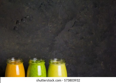 Healthy colorful fruit smoothie set on a dark background