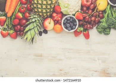 Healthy colorful fruits vegetables berries, strawberries oranges plums grapes broccoli cauiliflower mango persimmon pineapple on white wooden table, top view, copy space, toned, selective focus