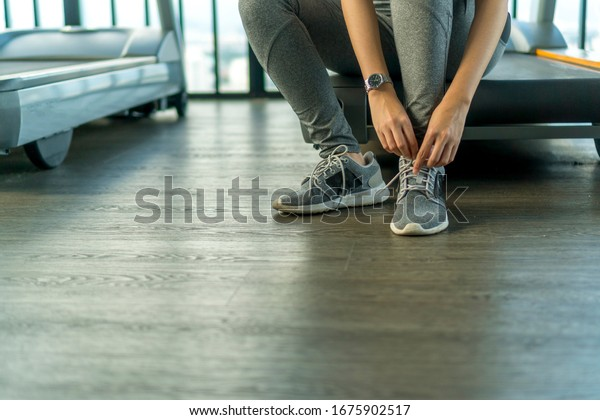 Healthy Concept, Closeup of cute Asian girl at the gym tying her shoes