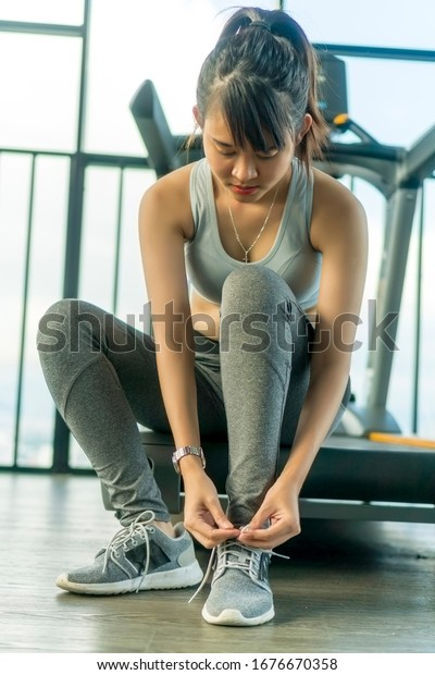 Healthy Concept, Cute Asian girl at the gym tying her shoes