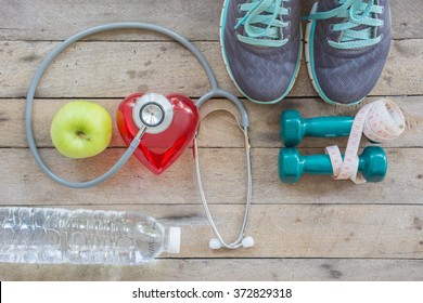Healthy concept , diet plan with sport shoes and bottle of water and Dumbell on wooden background