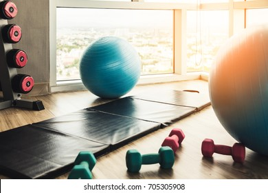 healthy concept with fitness center dumbbell rack and yoga ball with exercise mat on wooden floor with background of blue sky