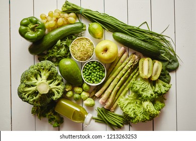 Healthy concept with green antioxidant organic vegetables, fruits and herbs and bottle of fresh smoothie. Placed on white wooden table. With copy space.