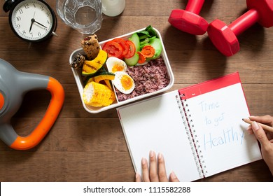 Healthy concept with nutrition food in lunch box and fitness equipments with woman writing time to get healthy on diary book