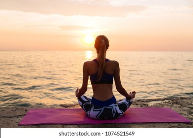 Healthy concept. View from back of sportive woman meditating in lotus pose, sitting on the pier, looking at sea sunset, enjoying the yoga.