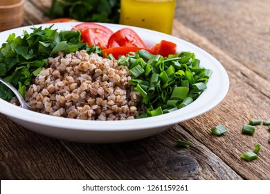 Healthy cooked buckwheat grain salad with fresh green onion, parsley and tomatoes, olive oil and lemon juice dressing, plant based food, selective focus