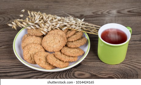 Healthy cookies and mug with hot tea on a wooden background. Pastry from oat flakes with decorative dry oats and the drink with smoke.