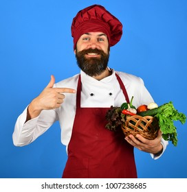 Healthy cooking concept. Chef holds lettuce, tomato, pepper and mushrooms. Man with beard on blue background. Cook with smile in burgundy uniform points at vegetables in wicker bowl.