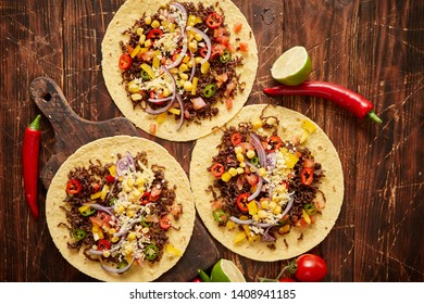 Healthy corn tortillas with grilled beef, fresh hot peppers, cheese, tomatoes over rusty wooden table background, top view, copy space. Mexican food contept.