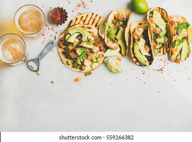 Healthy corn tortillas with grilled chicken, avocado, fresh salsa, limes and beer in glasses over light grey marble table background, top view, copy space. Gluten-free, allergy-friendly food concept