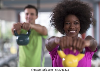 healthy couple  workout with weights lifting  dumbbells at  gym african  american woman with afro hairstyle