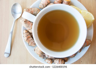 Healthy cup of hot turmeric tea with lemon flat lay