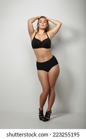 . Healthy and curvaceous sexy female model in black underwear with her hands in hair over grey background.