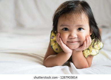 healthy cute little asian girl toddler smiling on bed. concept of happiness, childhood and lifestyle