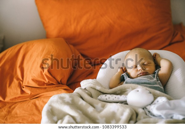 Healthy daytime sleep for the newborn. The baby is sleeping in the orthopedic Baby Cocoon on the bed.