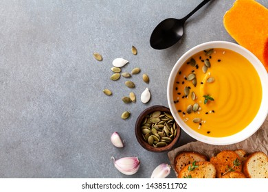 Healthy and delicious autumn pumpkin cream soup in bowl served with seeds and crouton on stone table top view.