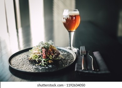 Healthy and delicious beef sandwich on dark table with glass of beer at restaurant, chef making food.