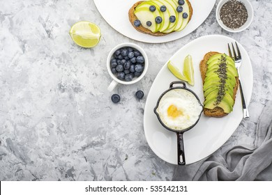 Healthy delicious breakfast of fried eggs in a batch frying pan and toast with green apple and avocado with blueberries on a marble background. Color year. Greenery. Top view