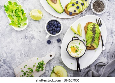 Healthy delicious breakfast of fried eggs in a batch frying pan and toast with green apple and avocado with blueberries on a marble background. Color year. Greenery. Top