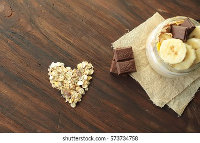 healthy delicious dessert - muesli and yogurt with banana, nuts and chocolate on dark wooden background