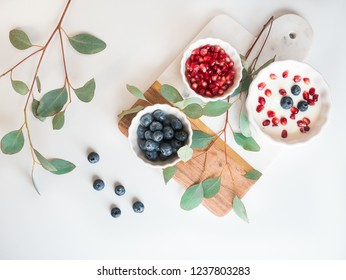 healthy and delicious snack with modern interior - yoghurt desert and berries (blueberry and pomegranate), wooden and marble background, beautiful eucalyptus branches