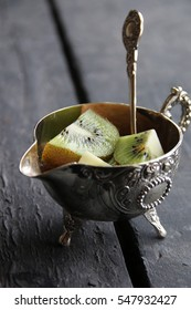 Healthy dessert with Kiwi fruit on silver bowl. Food background.