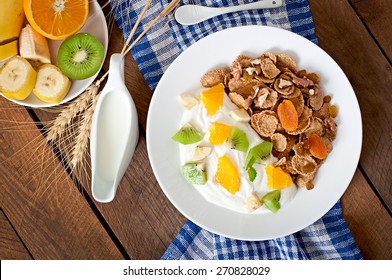 Healthy dessert with muesli and fruit in a white plate on the table. Top view.