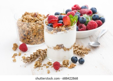 healthy dessert with natural yogurt, muesli and berries on a white table, horizontal