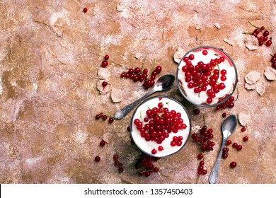 Healthy dessert with organic red currants, fresh yogurt and corn flakes. Dietary breakfast on a brown background