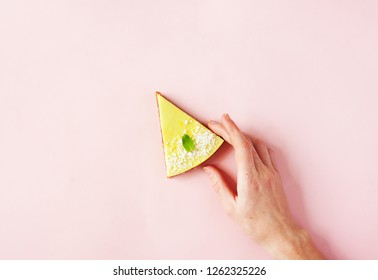 Healthy dessert - raw vegan lemon and coconut cake on pink background with woman hand - modern summer food minimal concept, copy space