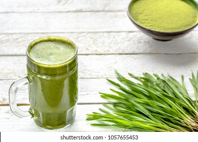Healthy detox drink with green barley grass, organic juice in jar on wooden background