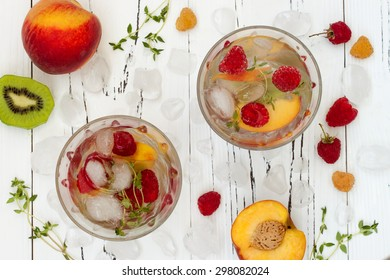 Healthy detox fruit infused flavored water. Top view. Summer refreshing homemade cocktail with fruits and thyme on white wooden table