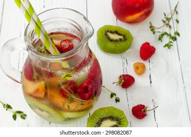 Healthy detox fruit infused flavored water. Summer refreshing homemade cocktail with fruits and thyme on white wooden table