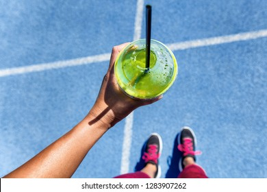 Healthy detox green smoothie cup food selfie pov showing running track and runner girl with shoes ready to run. Square social media instagram crop.