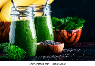 Healthy detox green smoothies with spinach, banana and chia seeds, brown background, selective focus