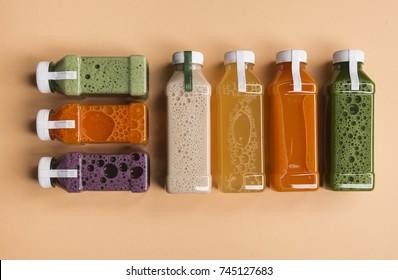 Healthy detox juice in plastic bottles on soft orange background. Colorful bottles. Healthy organic drink. Different tastes