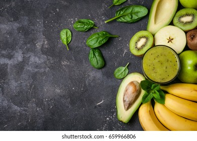 Healthy detox smoothie with kiwi, avocado, banana, apple and spinach. Green smoothie on grey background. Healthy food and diet concept. Copy space and top view